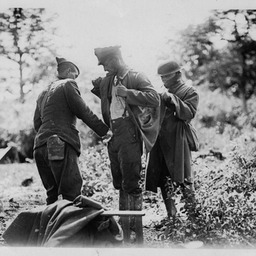 German POW being searched by American troops